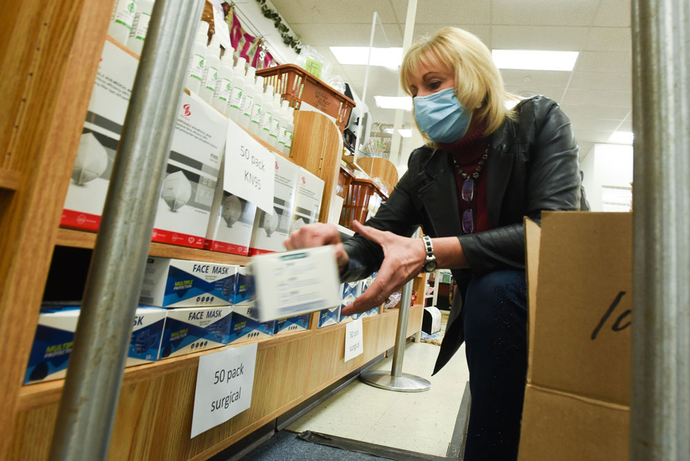 Laura Misiaszek, owner of The Olde Wicker Mill, organizes boxes of face masks. [Alex Cooper / Observer-Dispatch]